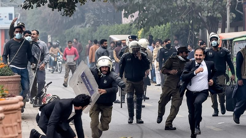 Policemen chase lawyers following a clash between lawyers and doctors in Lahore on December 11, 2019.