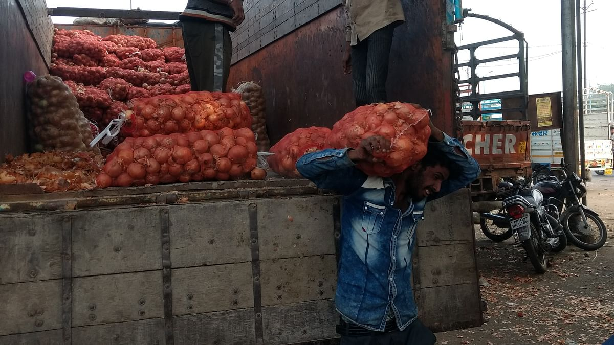 Workers off-loading imported onion at local Choithram mandi/ File Pic