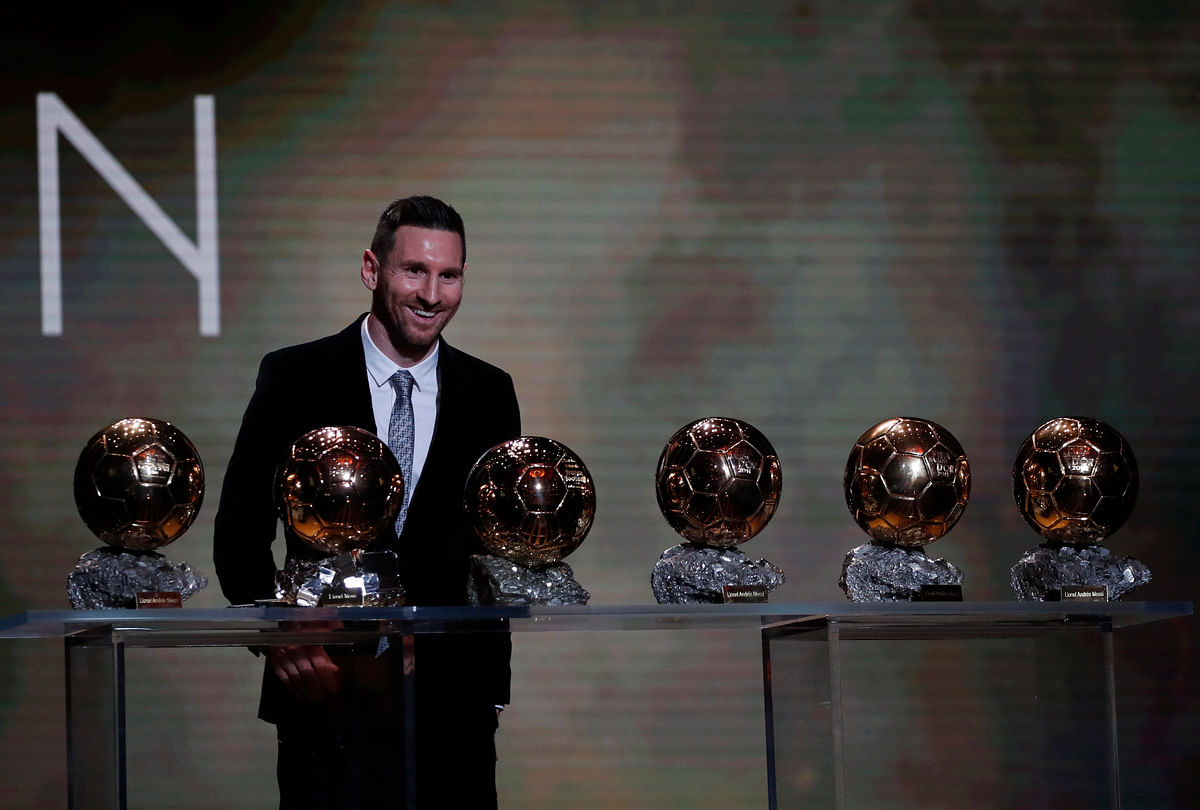 Barcelona's soccer player Lionel Messi poses with his six golden balls during the Golden Ball award ceremony in Paris.