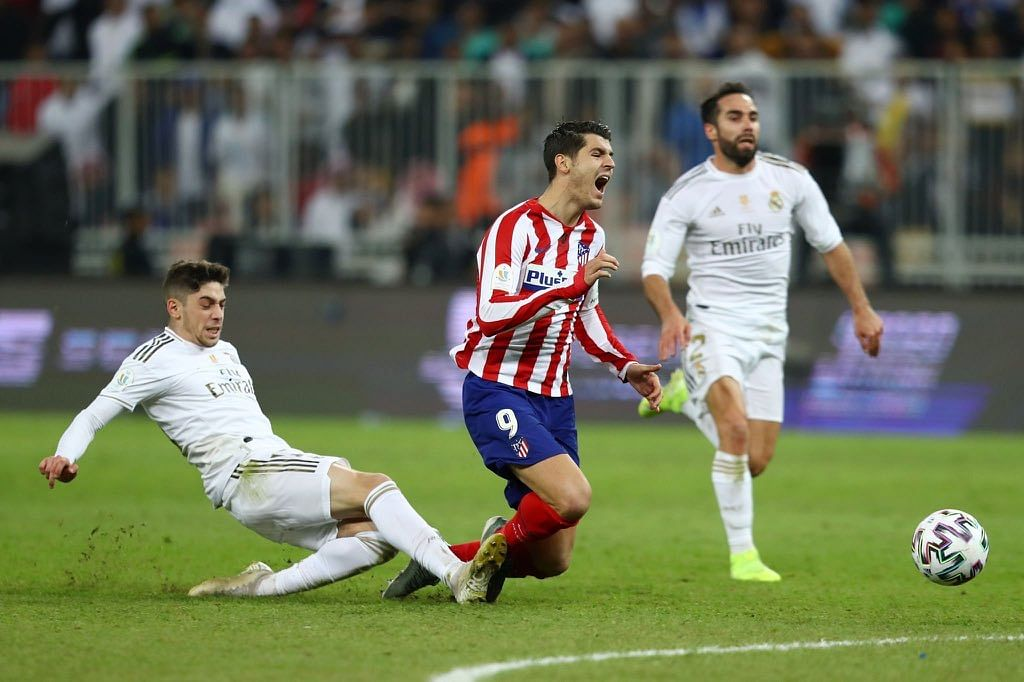 Fede Valverde of Real Madrid fouls Atletico Madrid's Alvaro Morata.