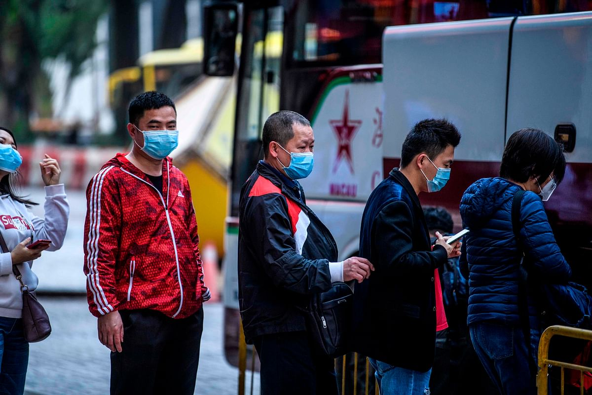 Tourists wear face masks as they prepare to board their tour bus outside the New Orient Landmark hotel in Macau on January 22, 2020, after the former Portuguese colony reported its first case of the new SARS-like virus that originated from Wuhan in China.
