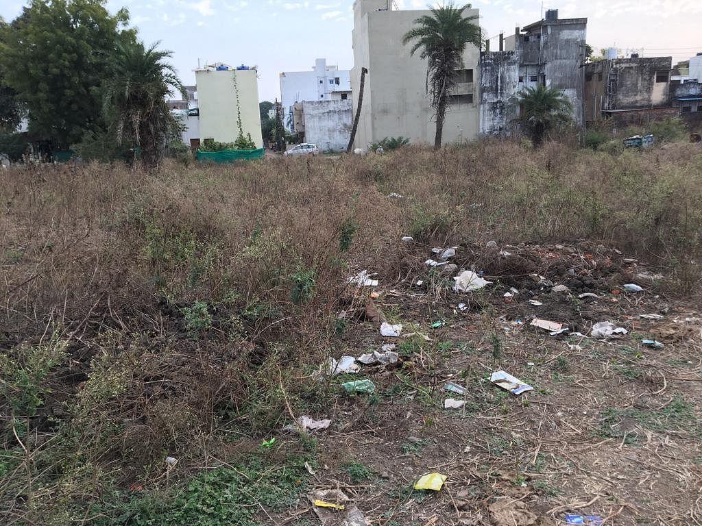 Eyesore: Making way through waist-high grass, strewn waste Rajharsh colony park in Bhopal