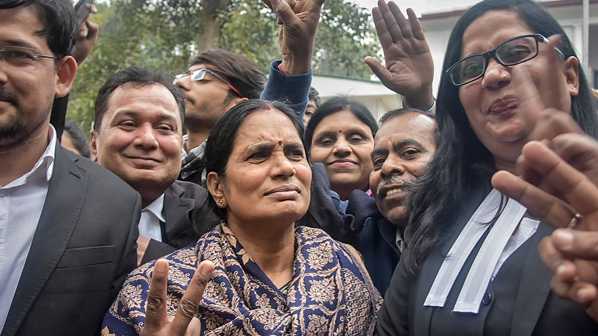 Nirbhaya case victim's mother flashes the victory sign along with lawyers after a court issued death warrants against the four convicts in the case, outside Patiala House Courts in New Delhi, Tuesday, Jan. 7, 2020.