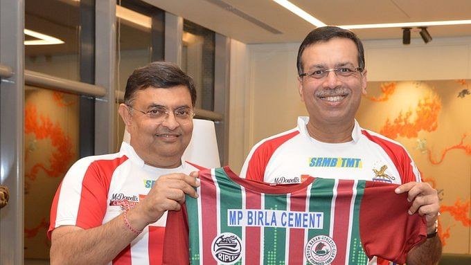 ATK owner Dr Sanjiv Goenka (right) with Mohun Bagan official holding the I-League club's jersey.