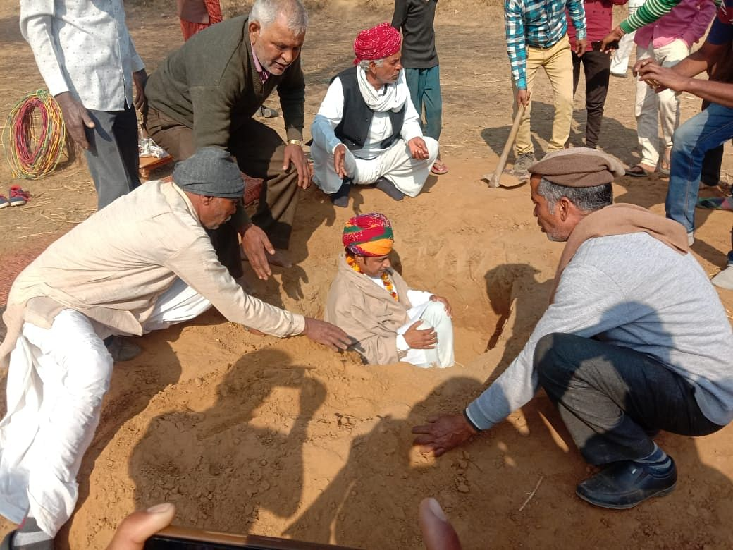 Buried in the earth farmers protest against acquisition of land for housing scheme