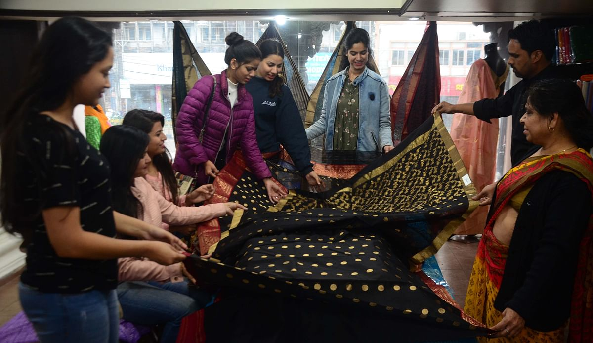 Women admiring a black Chanderi saree collection at GTB Mrignaynee Makar Sankranti Utsav-2020.