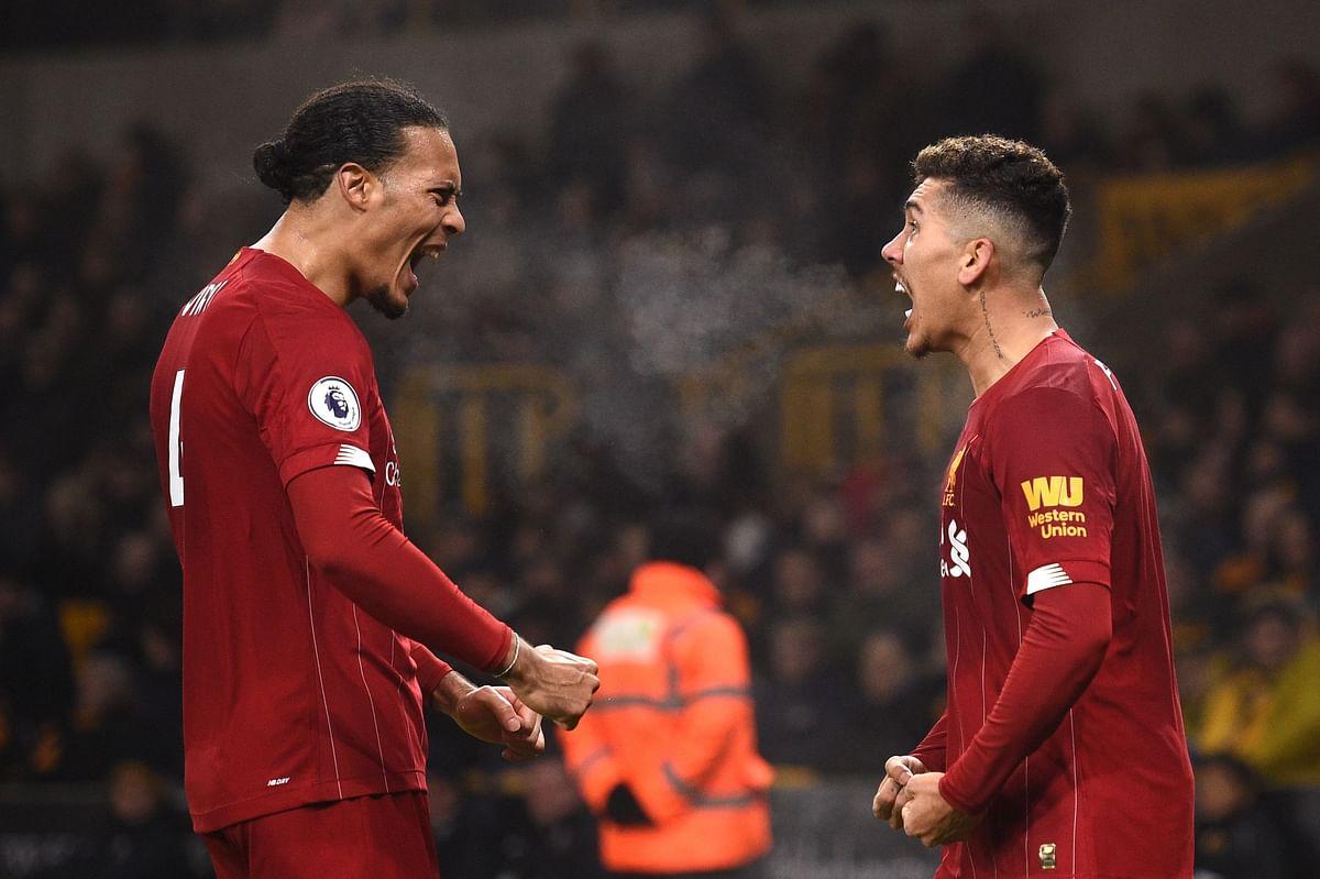 Liverpool's Brazilian midfielder Roberto Firmino (CL)  celebrates with teammate Virgil Van Dijk after scoring team's second goal against Wolverhampton Wanderers on Thursday.