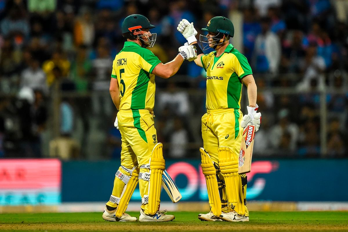 Australia's Aaron Finch (L) and teammate David Warner (R) celebrate after each scored a century (100 runs) during the first one day international (ODI)