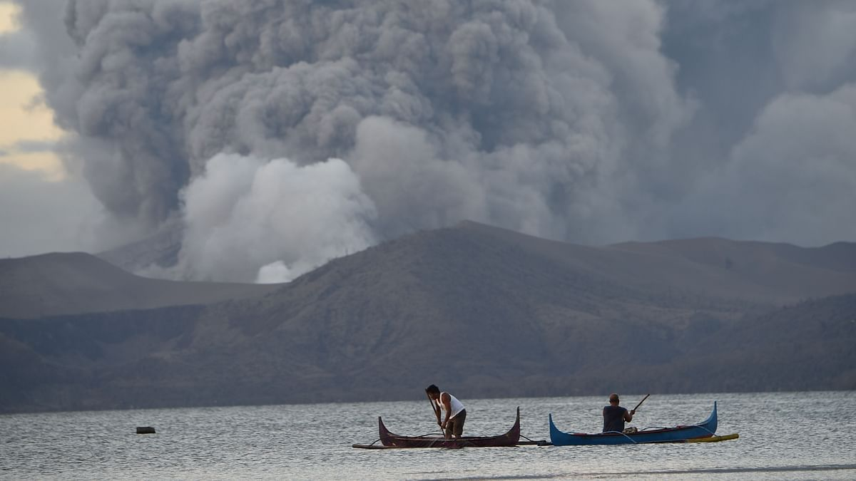 Residents living along Taal lake catch fish as Taal volcano erupts in Tanauan town, Batangas province south of Manila on January 14, 2020.