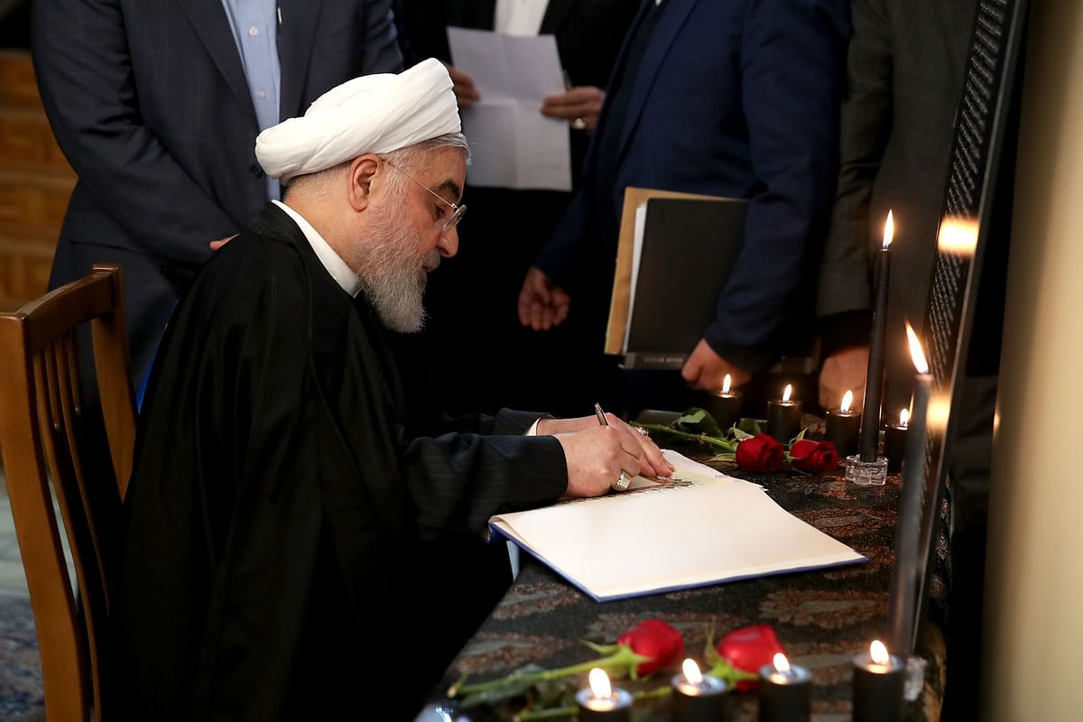A handout picture provided by the Iranian Presidency on January 15, 2020 shows President Hassan Rouhani signing a book carrying the names of the victims of the Ukraine Flight 752 downing, following a cabinet meeting in Tehran.