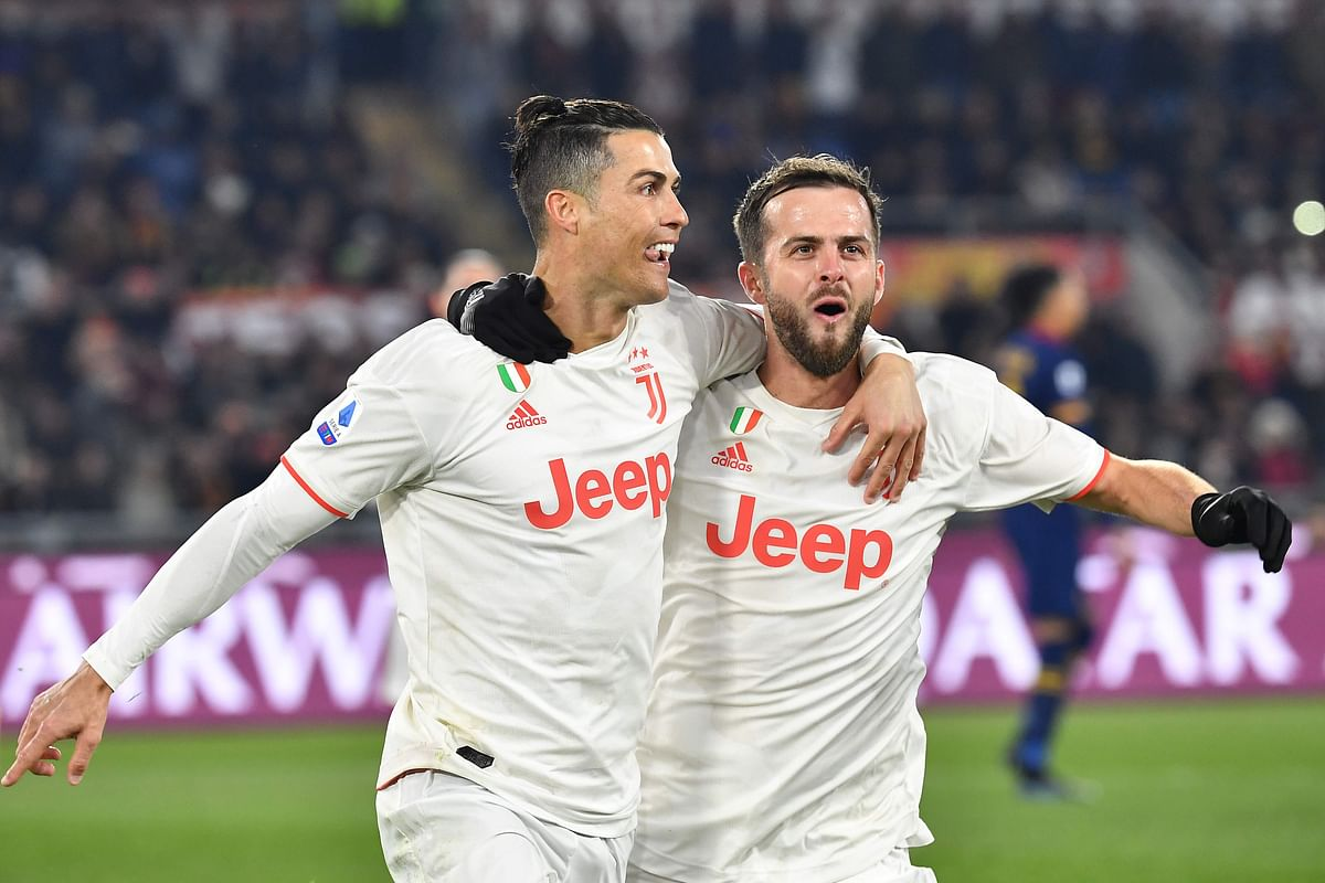 Juventus' Portuguese forward Cristiano Ronaldo (L) celebrates with Juventus' Bosnian midfielder Miralem Pjanic after scoring a penalty during the Italian Serie A football match AS Roma vs Juventus on January 12, 2020 at the Olympic stadium in Rome.