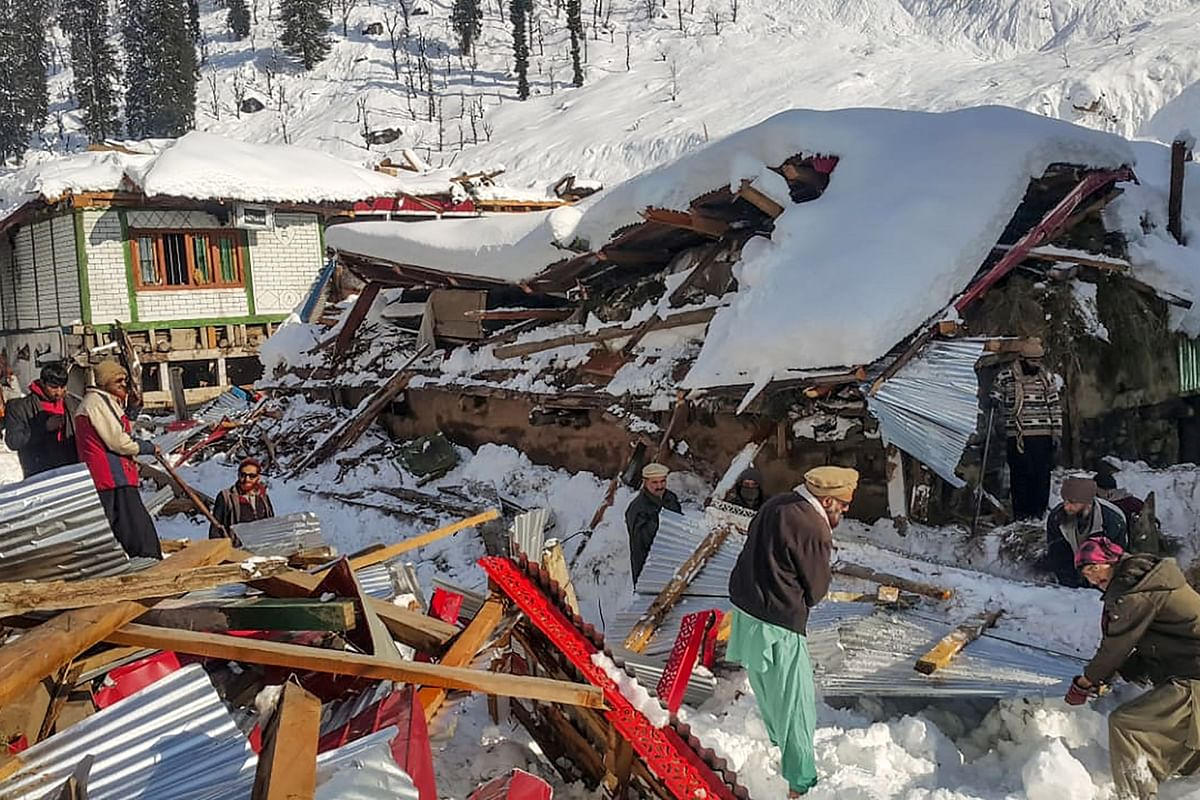 Local residents remove debris of a collapsed house following heavy snowfall that triggered an avalanche in Neelum Valley, in Pakistan-administered Kashmir on January 14, 2020.