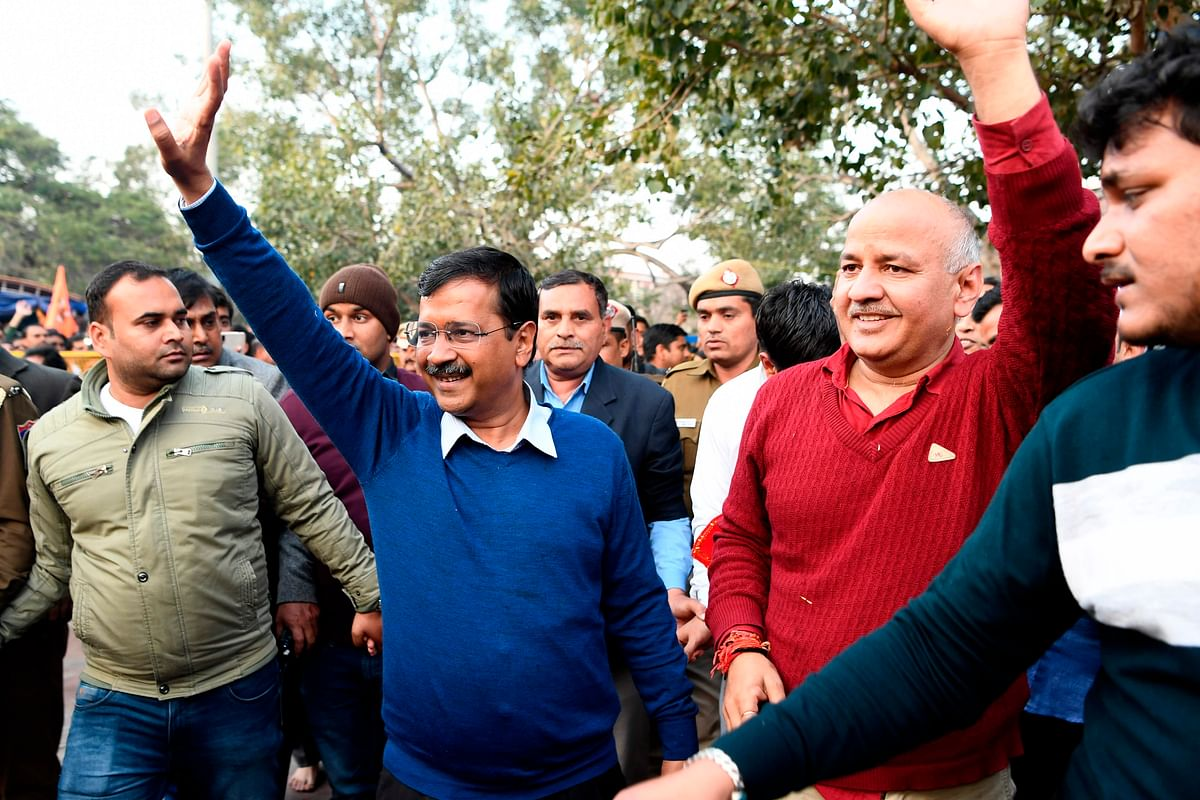 Aam Aadmi Party (AAP) chief Arvind Kejriwal (C) along with deputy Manish Sisodia waves after paying his respect at the Hanuman Temple in New Delhi.