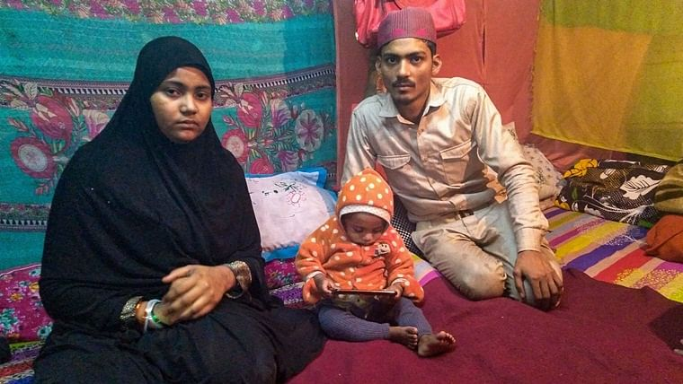 Mohammed Arif (R) and Nazia with one of their surviving children at their residence in Batla House, New Delhi