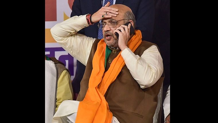 Union Home Minister Amit Shah speaks on the phone during an election campaign rally in support of BJP candidate Pravesh Ratan (unseen), ahead of the State Assembly polls, at West Patel Nagar in New Delhi, Tuesday, Feb. 4, 2020.