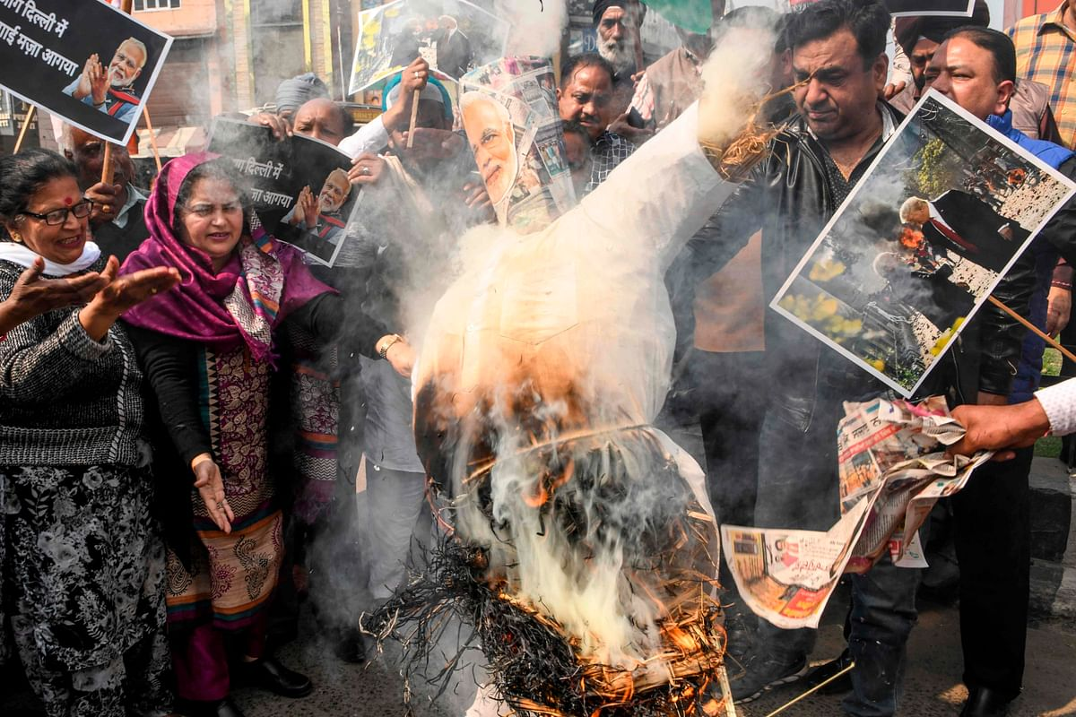 Congress Party workers shout slogans as they burn an effigy of India's Prime Minister Narendra Modi during a demonstration to protest against the violence occurring in New Delhi, in Amritsar on February 26, 2020