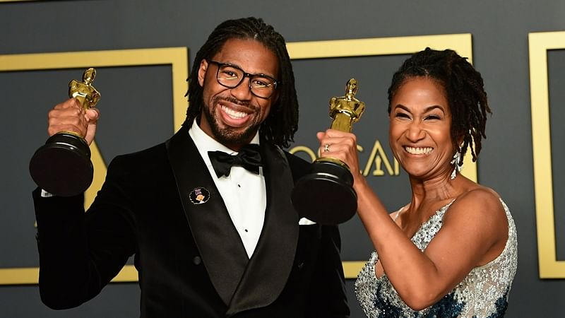 """US director Matthew A. Cherry and Karen Rupert Toliver poses in the press room with the Oscar for Best Animated Short Film for """"Hair Love"""""""