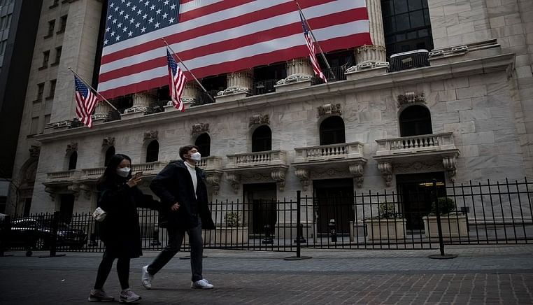 Pedestrians wearing face masks walk past the New York Stock Exchange (NYSE) in New York, the United States, on March 18, 2020.