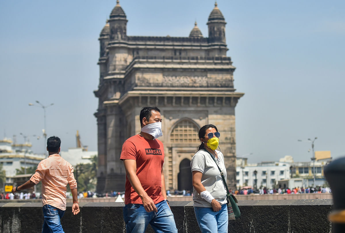 Tourists wear protective masks in view of  coronavirus pandemic at Gateway of India in Mumbai