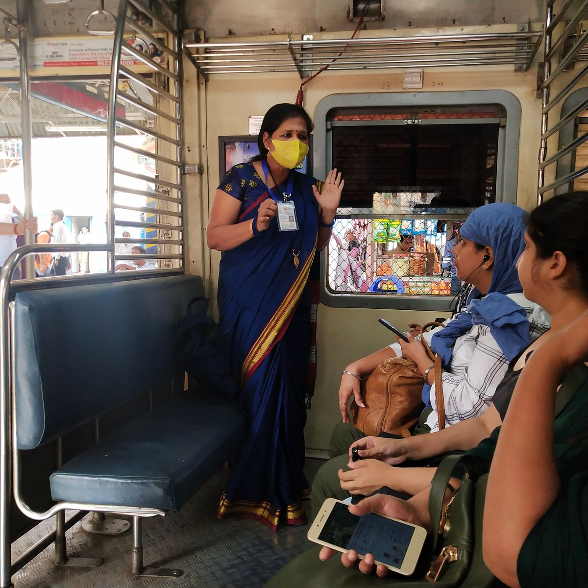 Central Railway staffer instructing passengers to  to use the mask