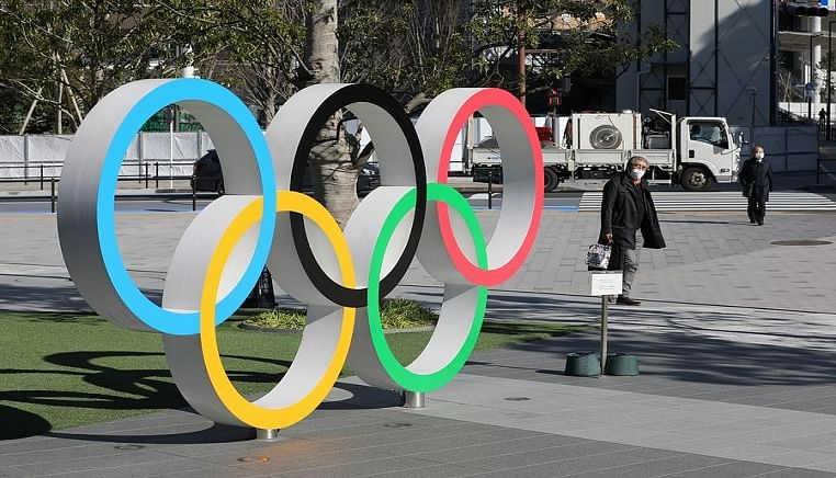 Pedestrians wearing masks walk past the Olympic rings in Tokyo, Japan, March 12, 2020.