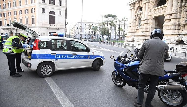 Policemen check a motorcyclist in Rome, Italy, March 22, 2020. The coronavirus epidemic continued to spread in locked-down Italy on Sunday with total cumulative number of infected cases reaching 59,138 and deaths reaching 5,476, according to the latest data released by the Civil Protection Department.