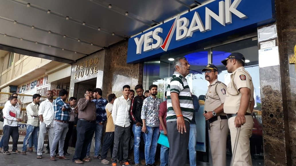 People stand outside a Yes Bank ATM on Friday