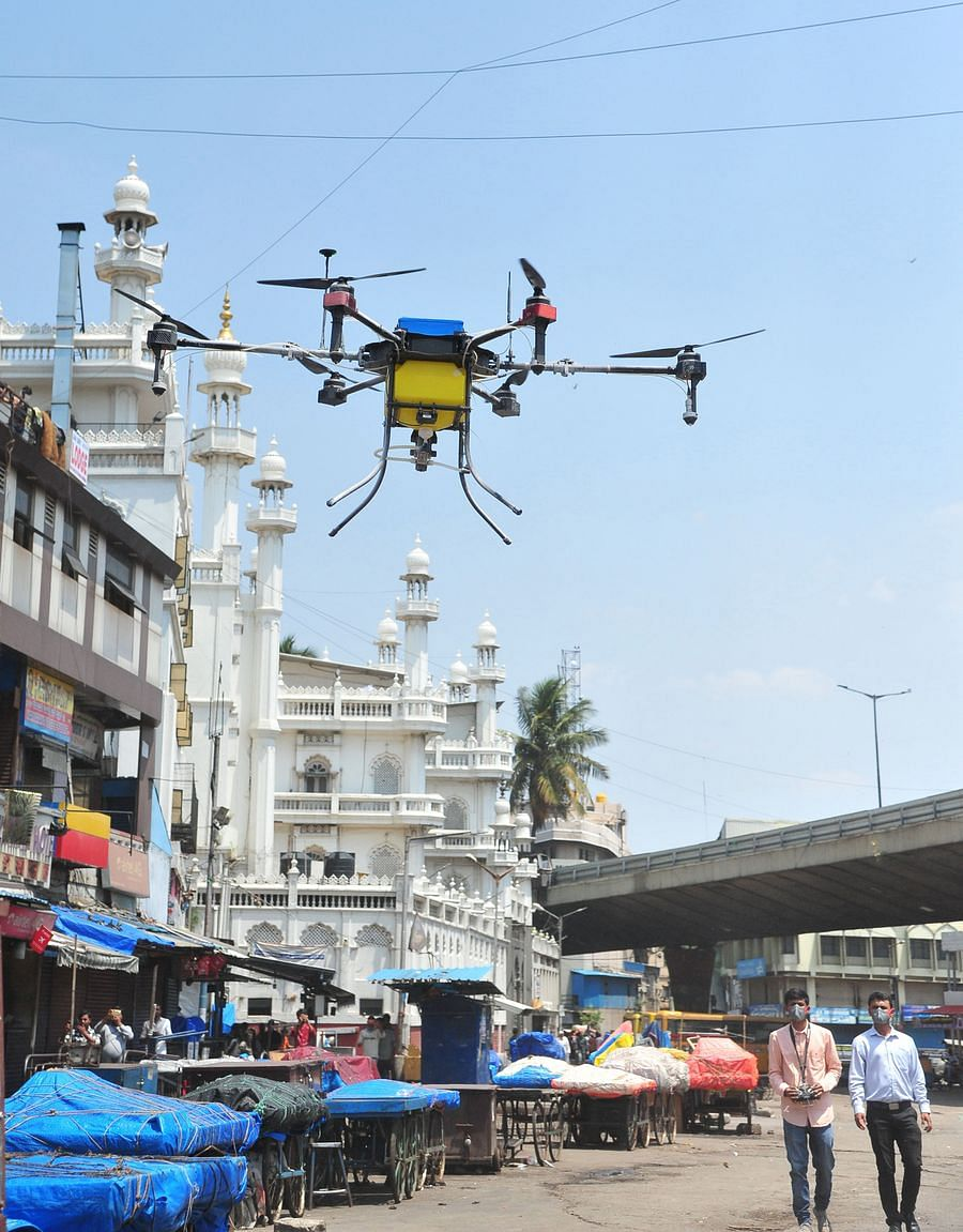 Indian private company workers fly a drone to spray disinfectant in Bangalore, India, March 24, 2020.