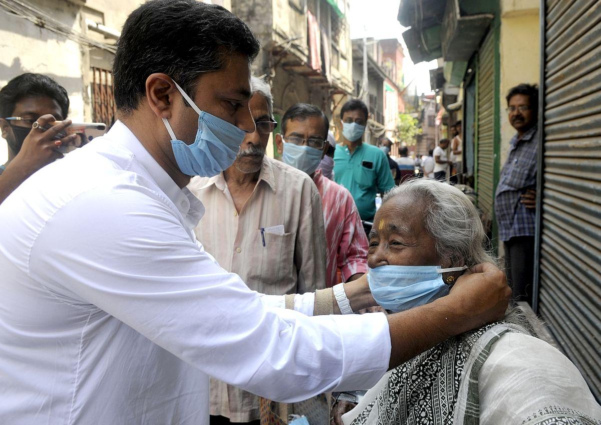 A Congress worker distributes a mask in Kolkata