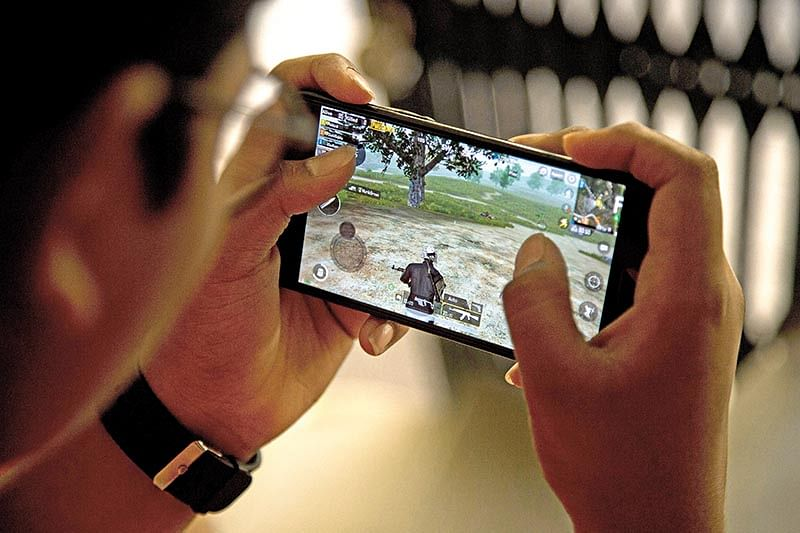 A boy playing a video game on his smartphone.