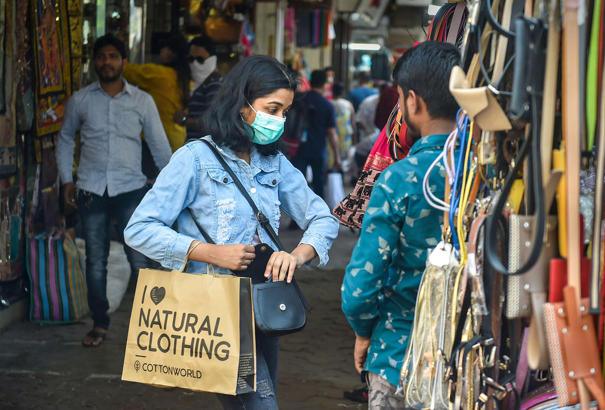 A woman wears a protective mask, in view of  coronavirus pandemic, as she shops at Colaba Causeway Market in Mumbai