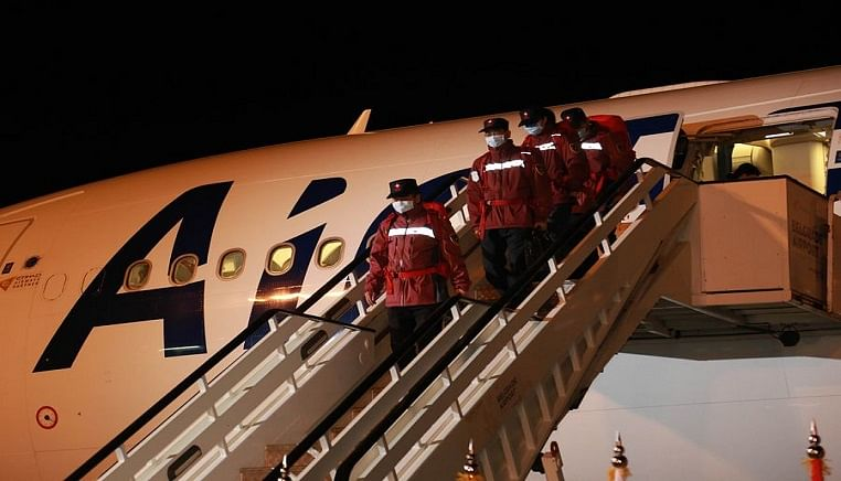 Chinese medical team members step off the plane upon arrival in Belgrade, Serbia, March 21, 2020.