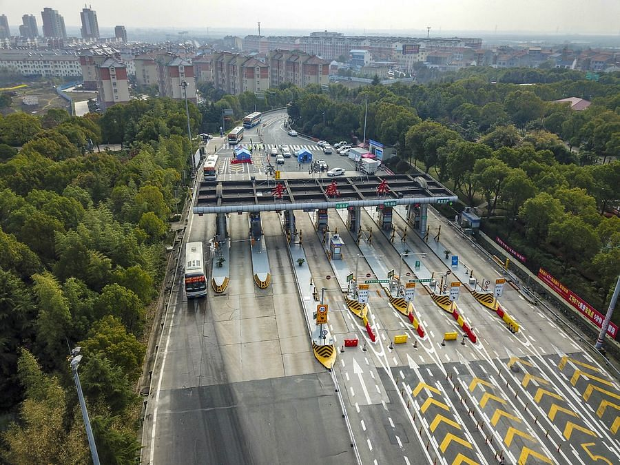 Chartered buses with workers passing a toll station in Xiaogan.