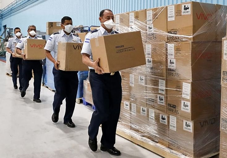 Officials of the Honduran Air Force carrying boxes containing medical equipment bought by the government from the US to treat patients infected with coronavirus