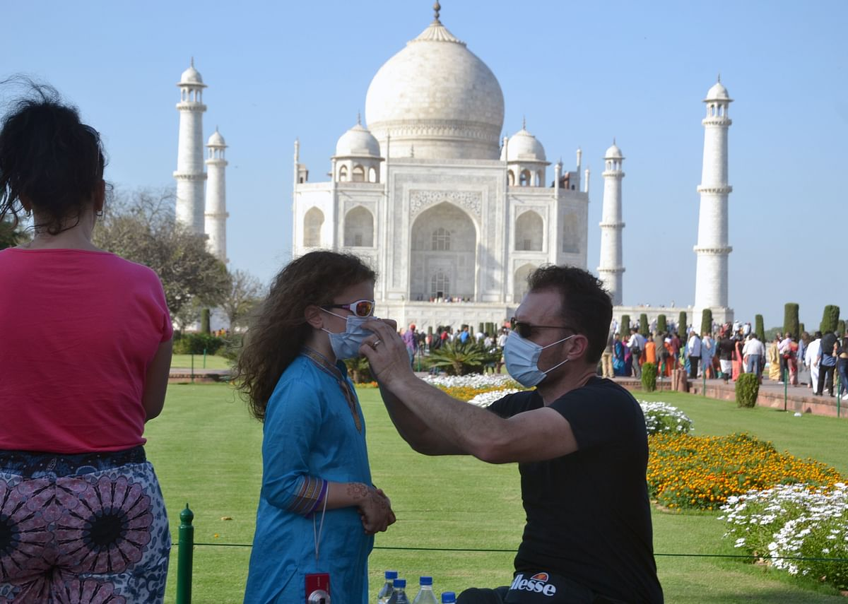 A foreign tourist put the mask on the girl's face to protect from coronavirus, during their visit to the Taj Mahal in Agra on Monday.