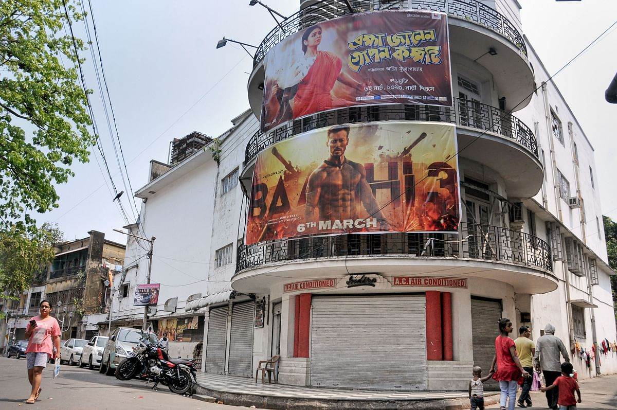 People walk past a cinema hall in Kolkata on Tuesday. One person tested positive in the city and many have been quarantined