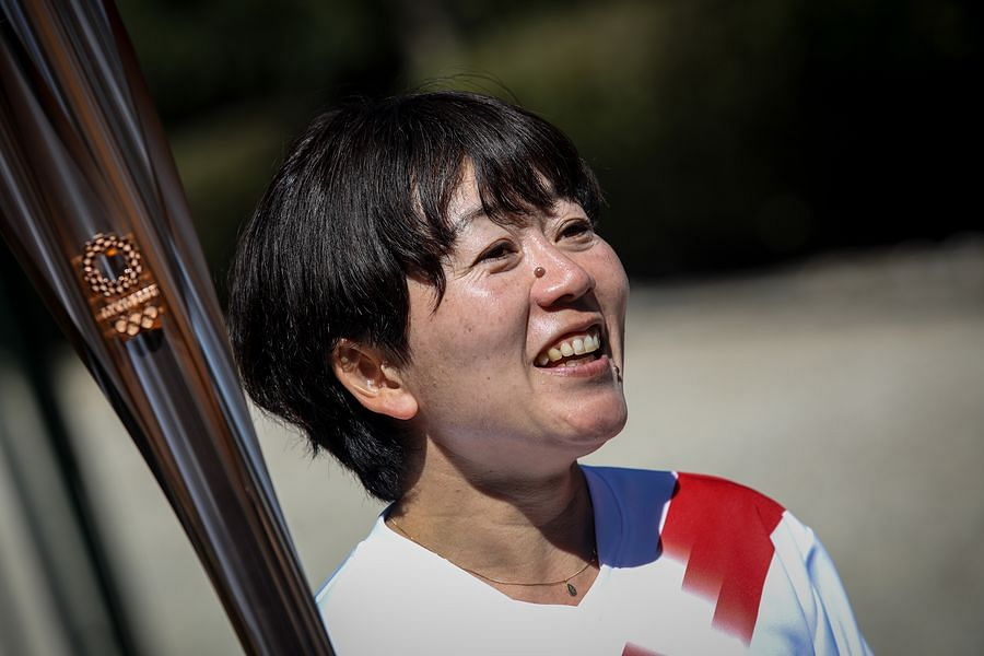 The second torchbearer Mizuki Noguchi, gold medalist in the women's marathon at the 2004 Athens Olympics, holds the torch after the flame lighting ceremony for Tokyo 2020 Olympic Games in Olympia, Greece, March 12, 2020.