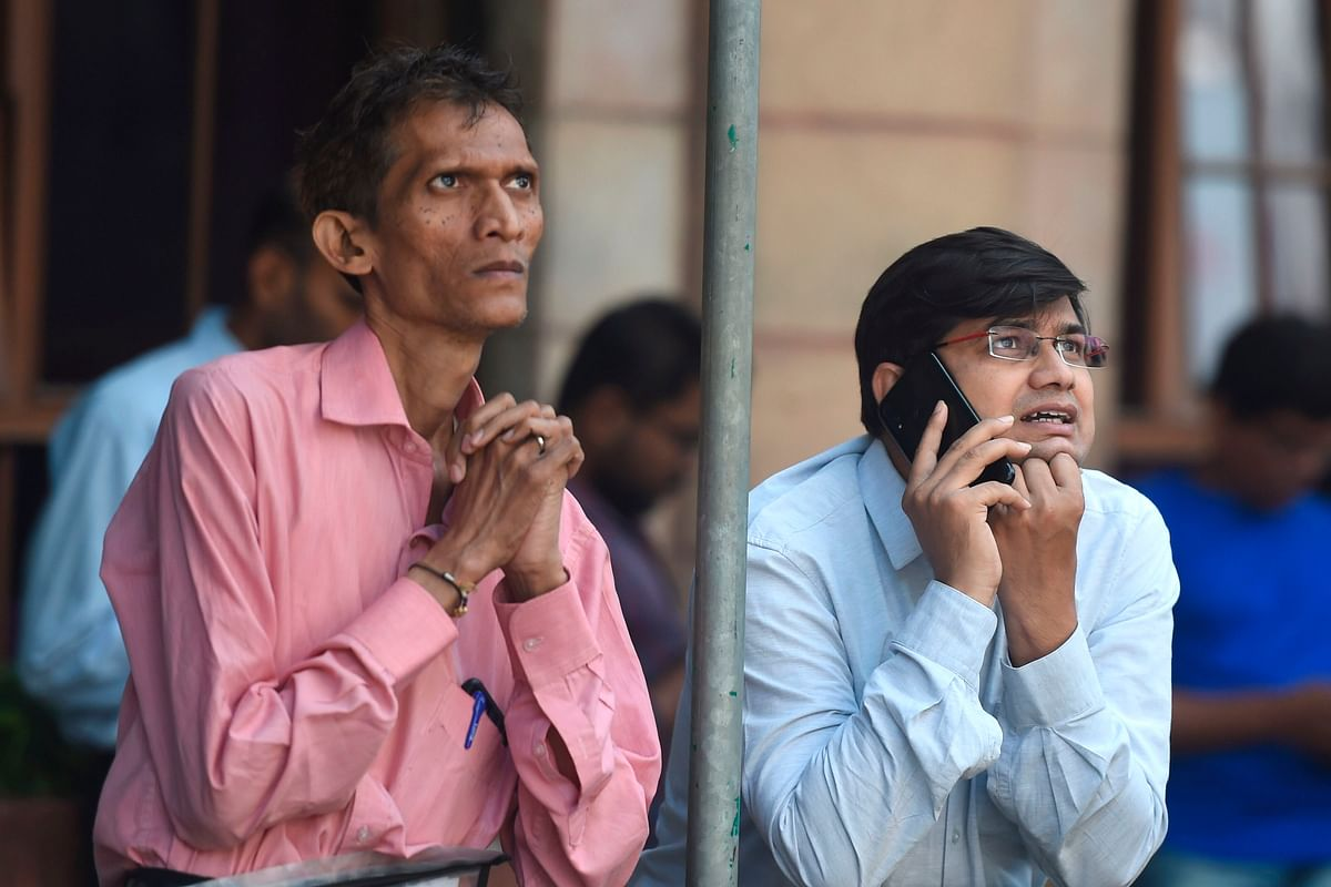 People wait outside Bombay Stock Exchange after the Sensex witnessed the worst drop in history