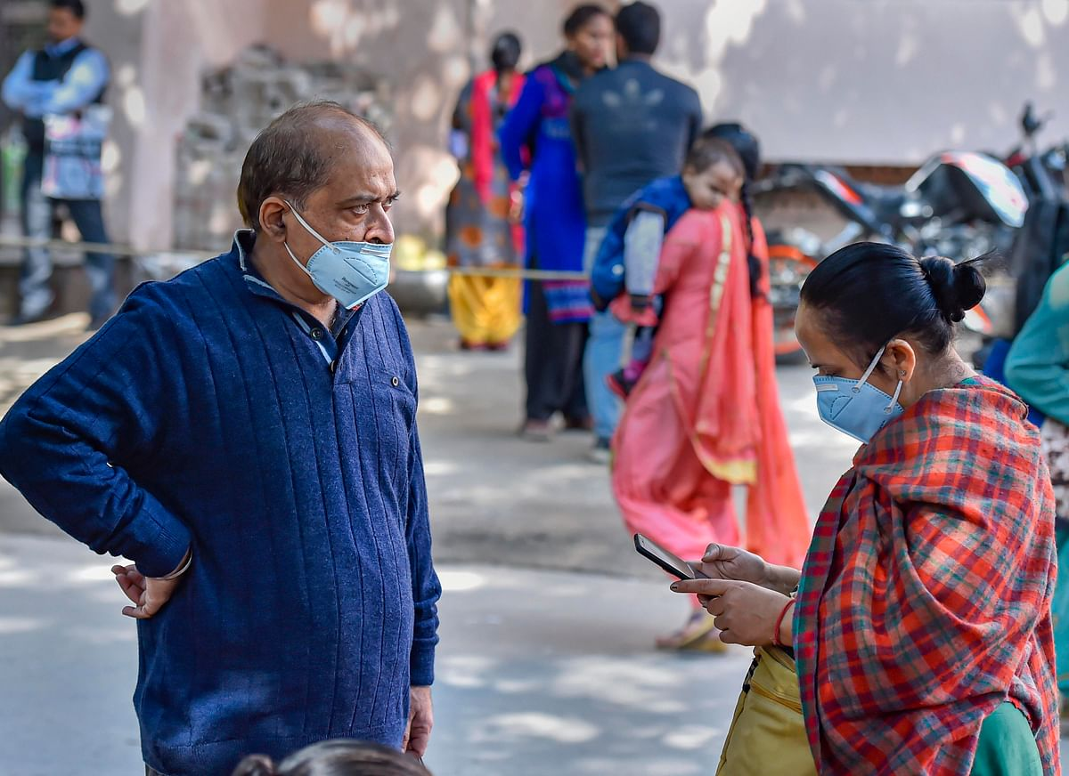 People wearing protective masks in the wake of novel coronavirus or COVID-19 outbreak, stand outside RML Hospital in New Delhi, Tuesday, March 3, 2020.