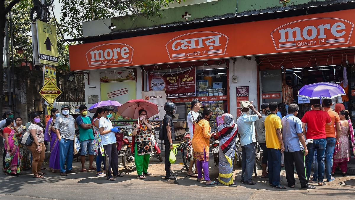 Locals stand in a queue to buy daily essentials before lock down amid rising concerns over the coronavirus pandemic, in Kolkata, Monday, March 23, 2020.