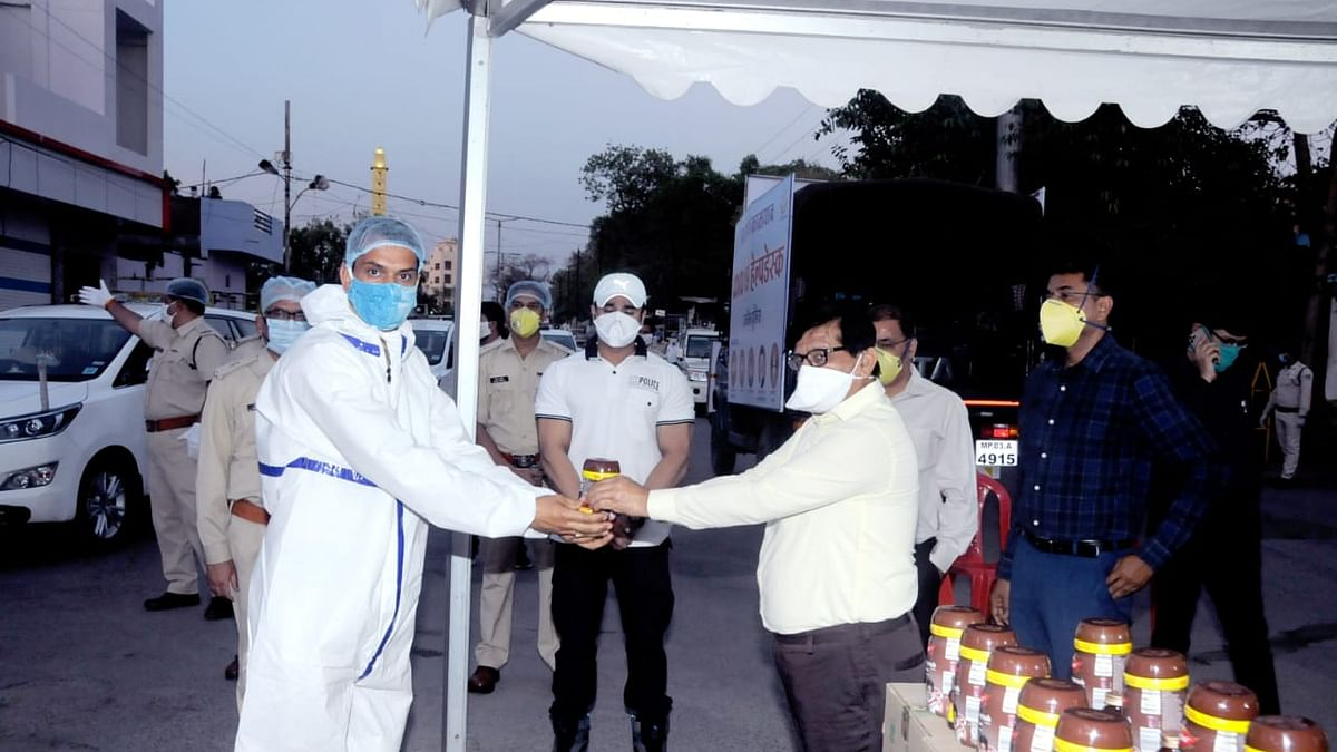 Divisional commissioner Anand Kumar Sharma presenting Chyawanprash and honey bottles to policemen on duty at the containment areas.