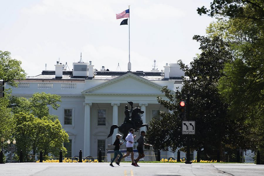 People jog near the White House in Washington D.C., the United States, on April 16, 2020.