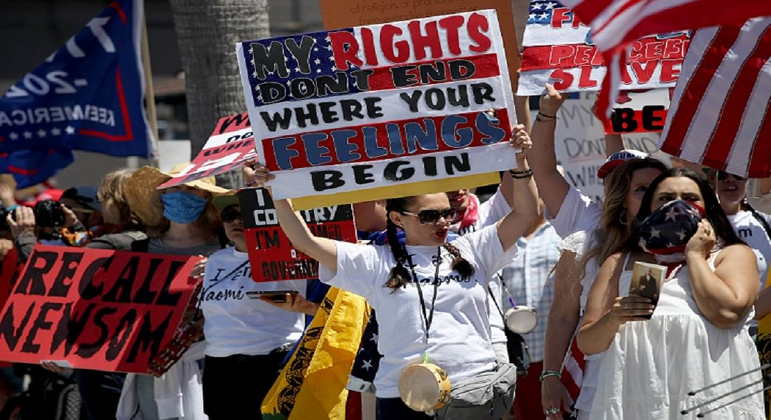 Protesters hold banners and chant against state government's measures for COVID-19 in San Diego, California.