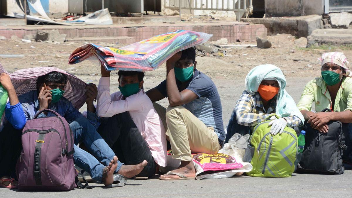 Long way home: Migrants queue for train tickets at Mumbai