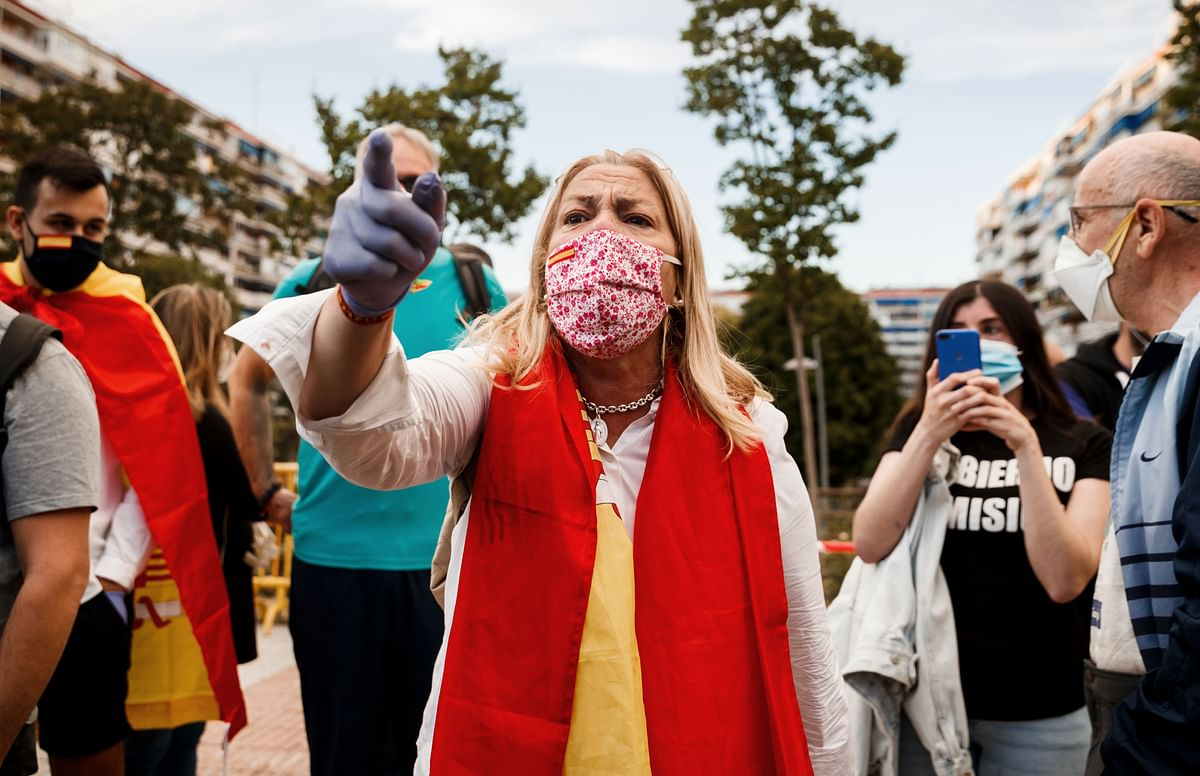 A woman wrapped in a Spanish flag shouts against counter protesters during a protest against government's handling of coronavirus crisis in Alcorcon, near Madrid.