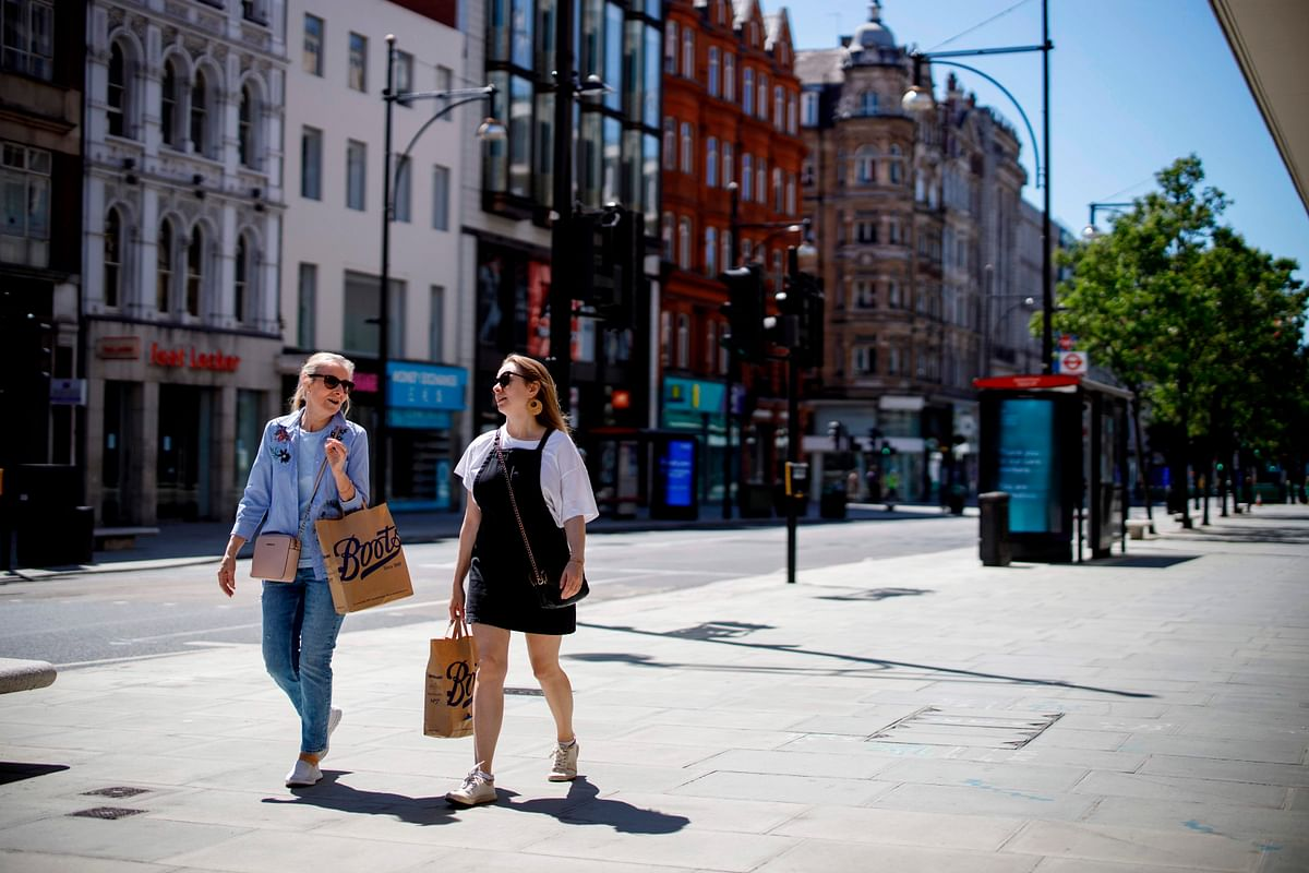 People walk past closed shops on Oxford Street in central London.