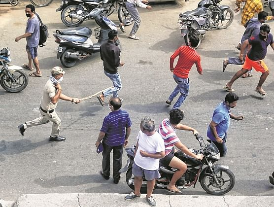 Police use force to disperse  violators outside a liquor shop, in  New Delhi on Monday.
