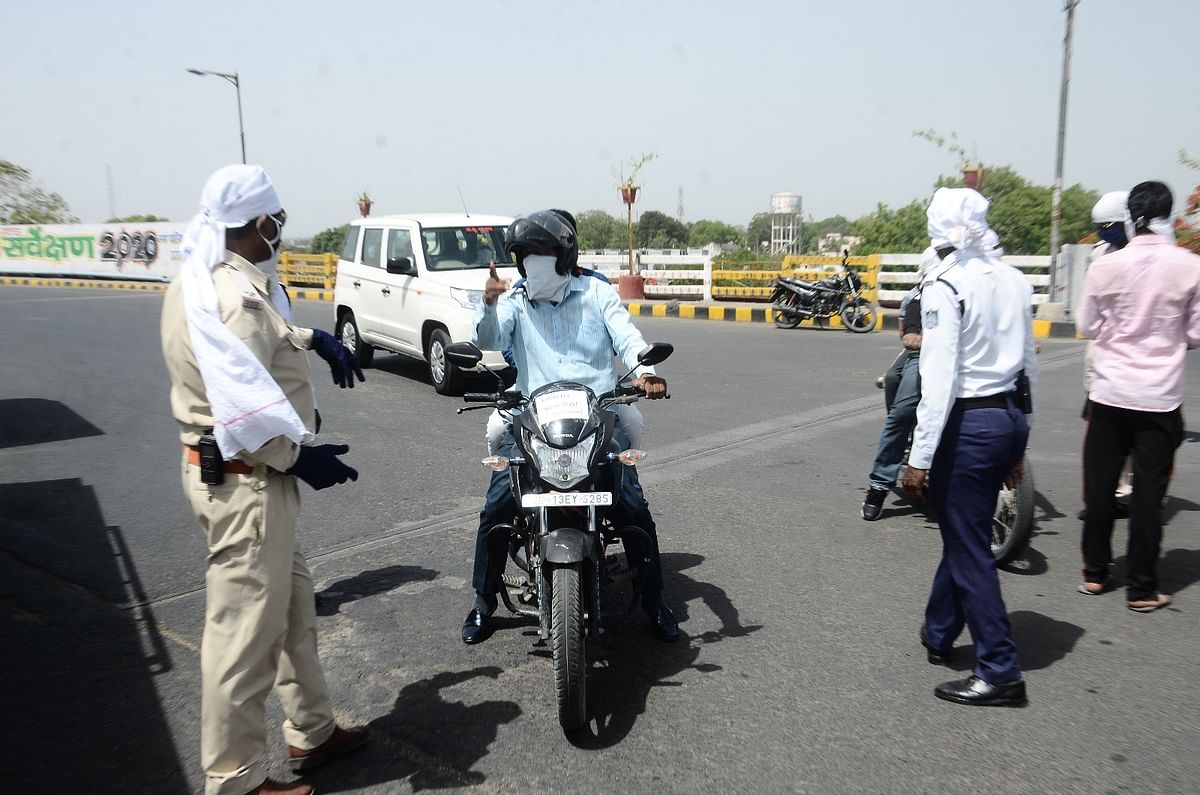 Cops interact with commuters on road in the outskirts of the city.