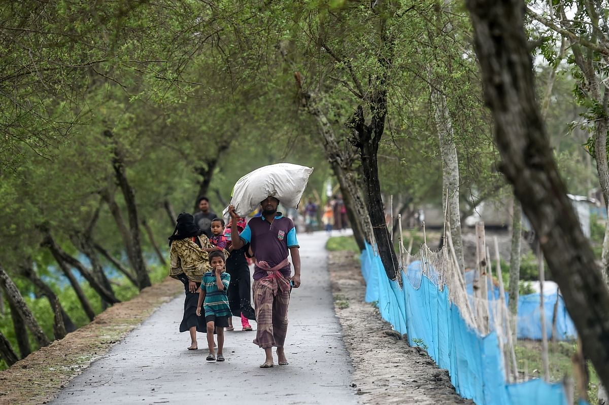 Residents walk along a street heading to a shelter ahead of the expected landfall of cyclone Amphan, in Dacope of Khulna district, Bangladesh