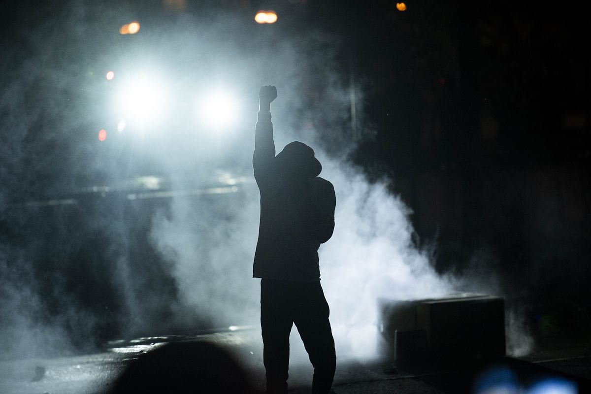 A protester holds up a fist in a cloud of tear gas outside the Third Police Precinct building on May 28, 2020 in Minneapolis, Minnesota